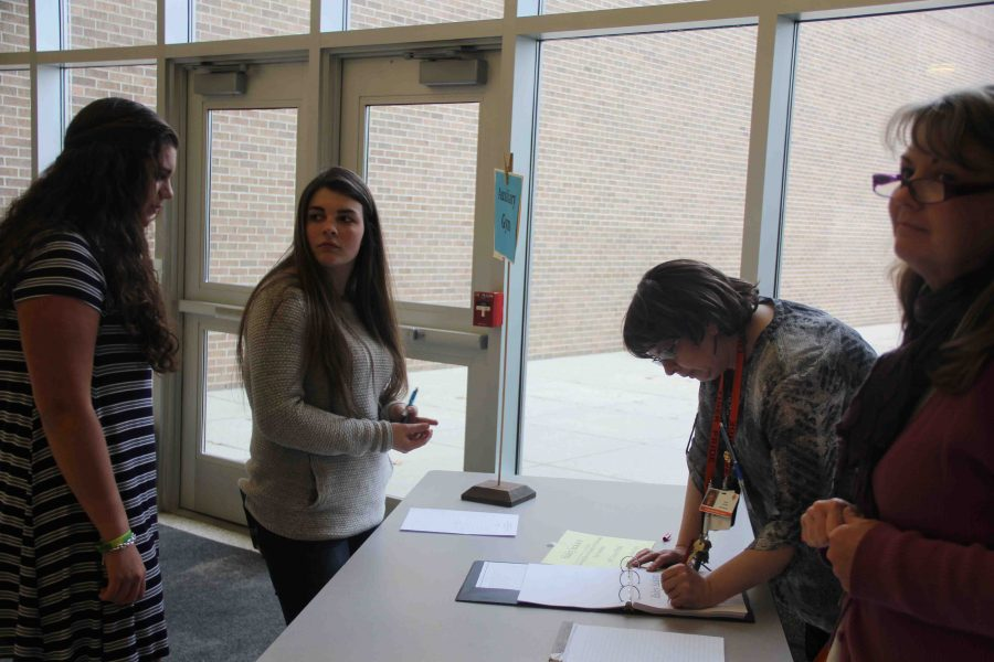 Before the Personal Project Exhibition, sophomore Skylar Matthews signs in to find out where her spot is for her project.