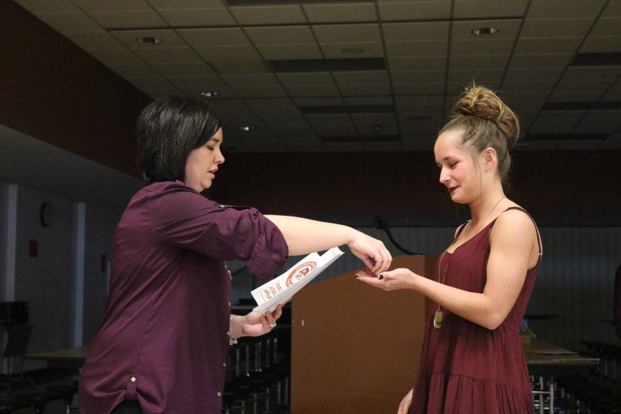 Walking up to her coach, senior Nina Lademan accepts her award at the varsity cheer banquet.