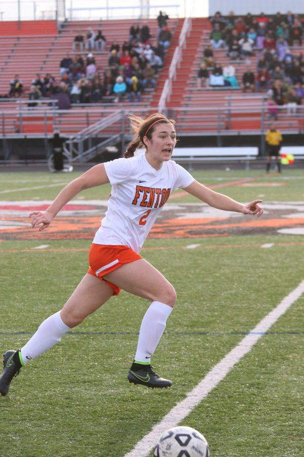 Running down the football field, sophomore Margaret Berry plays in her varsity soccer game.