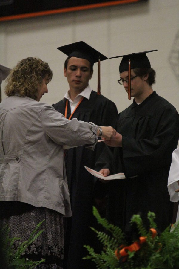 "2015 graduate Nick Farella receives his certificate and pin for being in the Top Ten at last year's academic honors assembly. The Class of 2016 will be the first in Fenton High history with the opportunity to graduate with Latin honors ""cum laude,"" ""magna cum laude"" or ""summa cum laude."" This switch was made because of the transition to weighted grades in advanced classes."