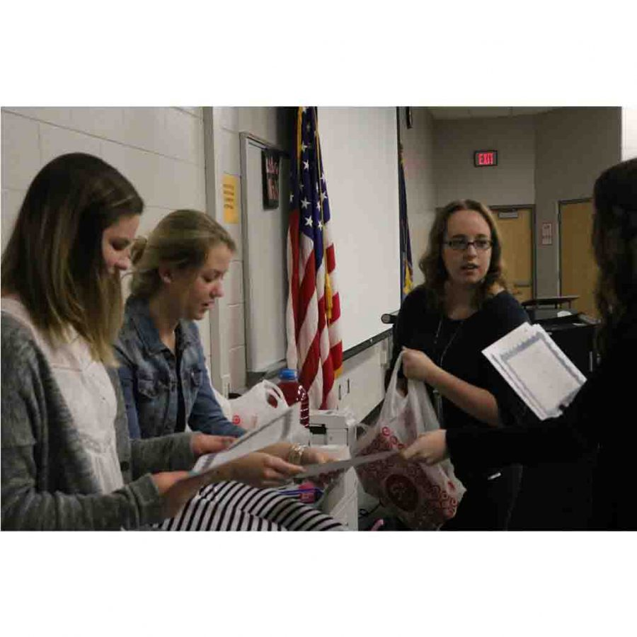 Talking to fellow Key Club members at the meeting last week, junior Kortney McQuarters talks about the Soles for Souls project.