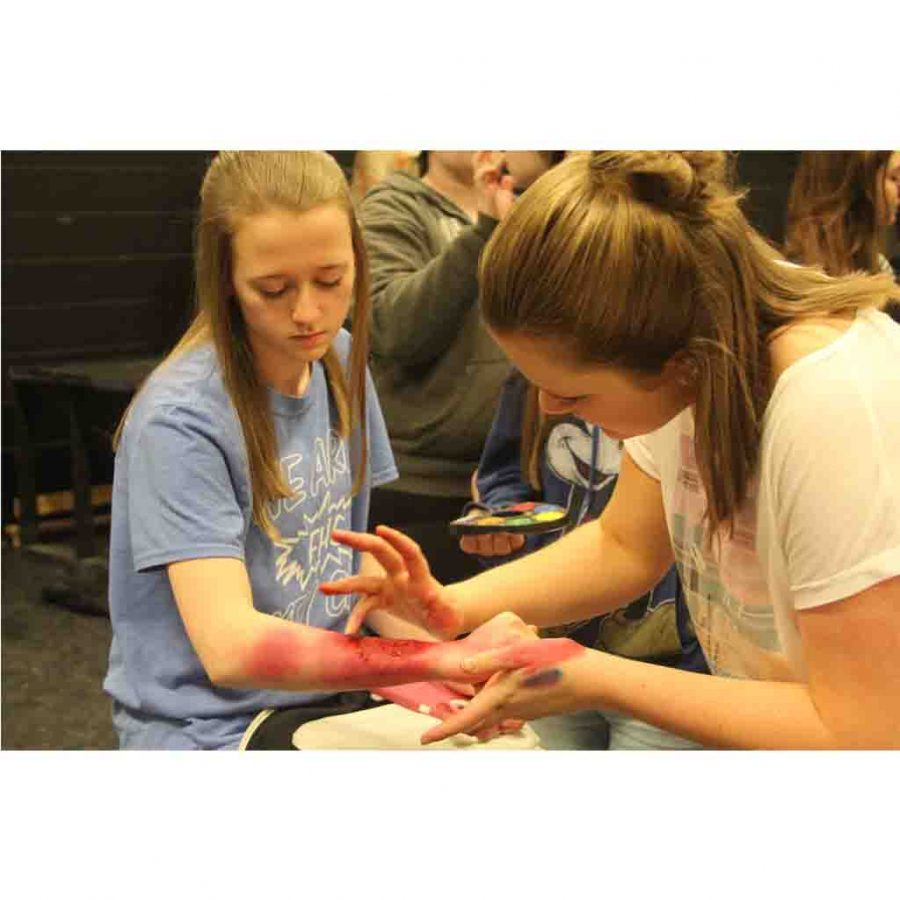In drama class, junior Samantha Cambell practices putting makeup on a friend to make it lol ok like she has a cut.