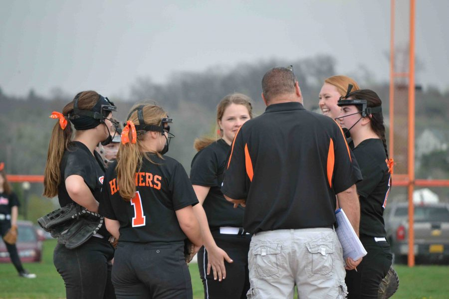 Huddled up on the diamond, freshman Chloe Billings listens to her coach give her and her teammates a pep talk at the JV softball game vs. Kearsley.