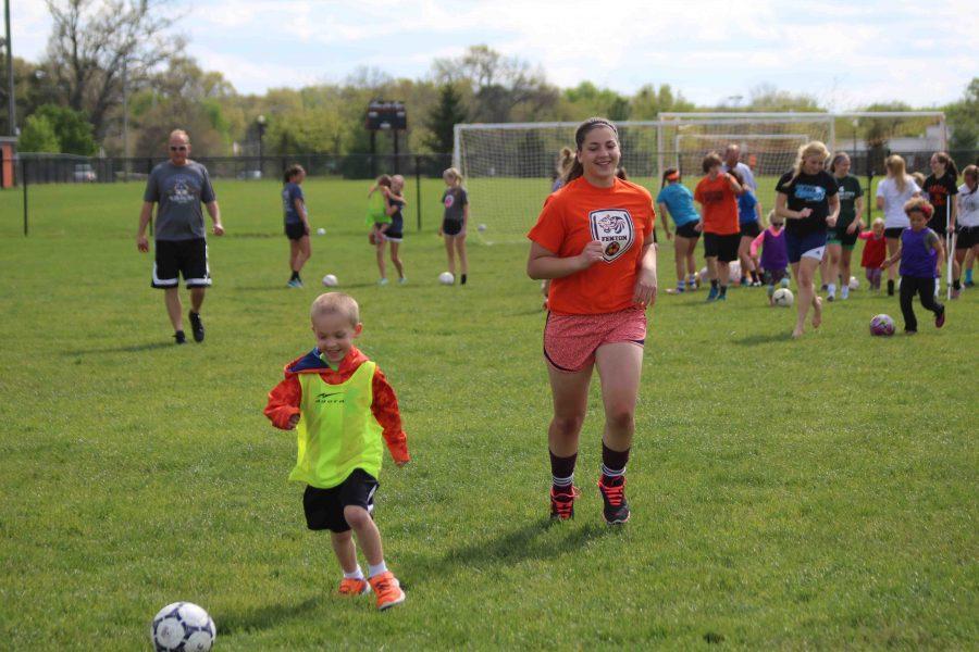 As she helps at the Little Tigers camp, freshman Lauren Klosoniak runs after a kid.