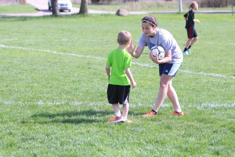 High fiving a little kid, freshman McKenzie Cassar helps run the Little Tigers camp put on by the soccer team.
