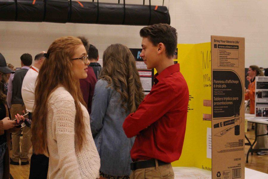 As he stands by his personal project, sophomore Antonio Zayas listens as his friend speaks.