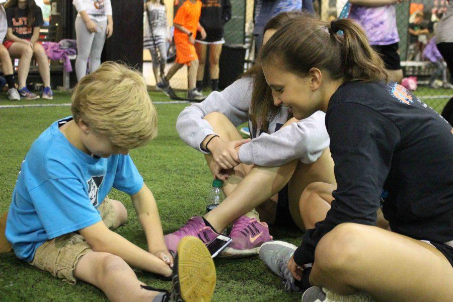 As she helps at Midnight Madness, junior Rachel Becker talks to a kid who is playing soccer at the event.