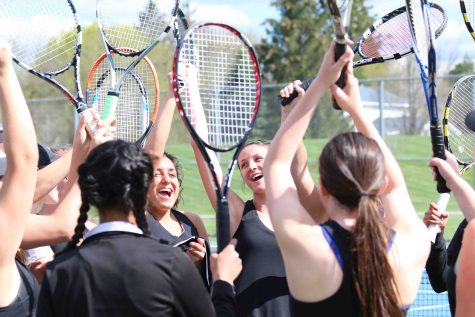 As they hold their rackets up, members of the varsity tennis team cheer after they win their match.
