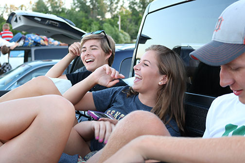 Savoring the last few weeks of summer, junior Rachael Rittichier jokes around with sophomore Caitlyn Dailey at the drive-in. The girls joined six of their friends to see the movie