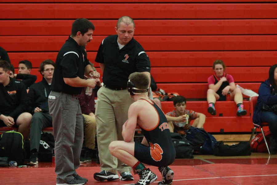 Coach Brad Beverly speaks to a player at their first meet of the season. He is qualified for the job with 10 years prior of high school coaching.