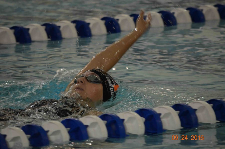 As she swims backstroke, sophomore Emma Snedden competes in the 200 yard Individual Medley at the Genesee County swim meet.