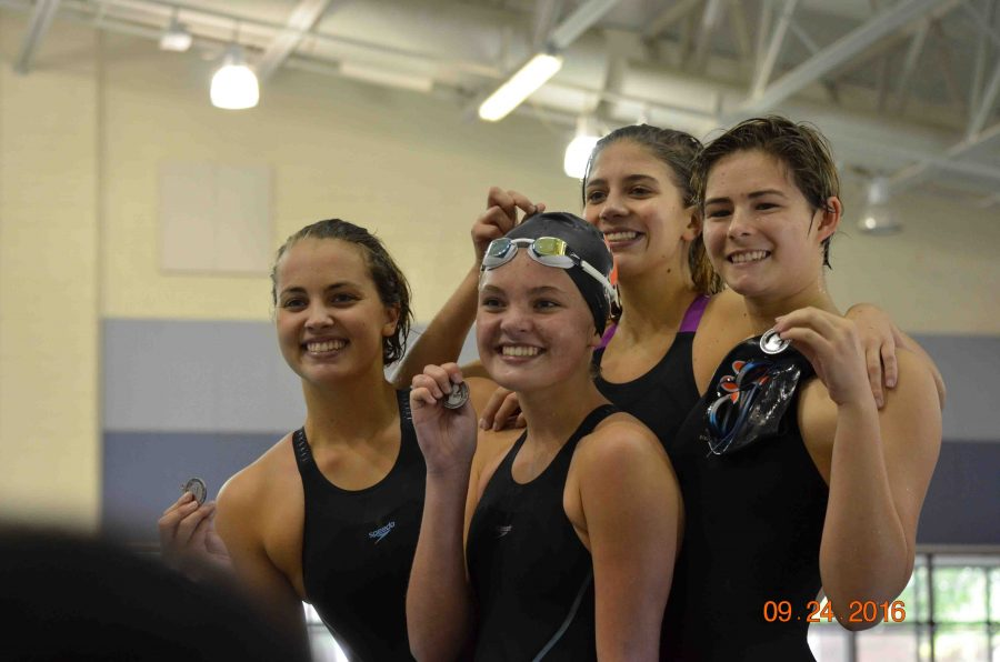 As she embraces her relay teammates, sophomore Sabrina Hall smiles from hearing good news from her coach.