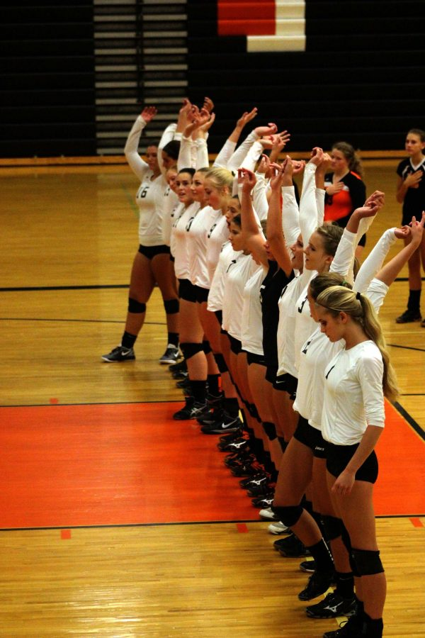 At the beginning of the volleyball game, the varsity girls stand for the national anthem. Following the famous anthem, the ladies swing their hands as they start to cheer.
