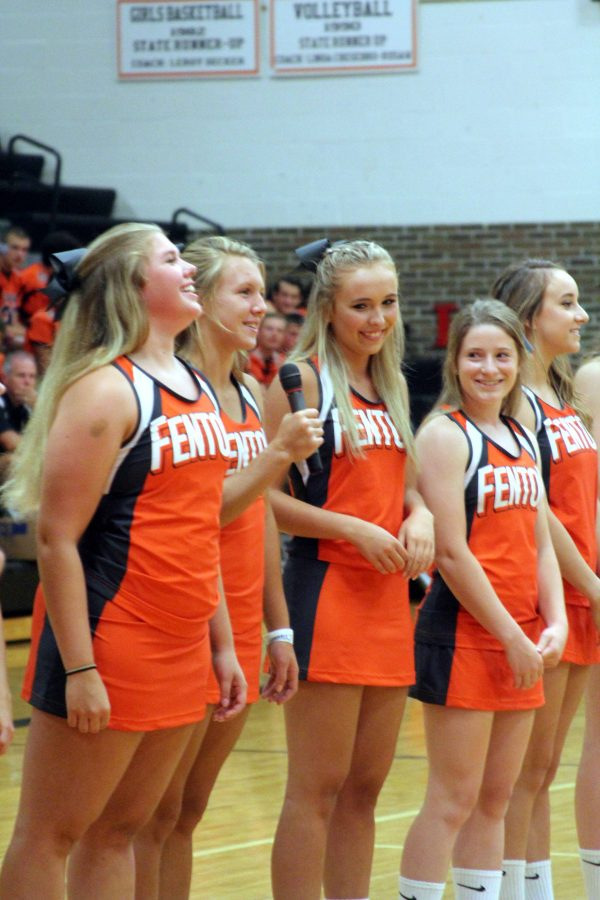 Laughing while junior Abby Koza, introduces herself, the Varsity Cheer team, stands in front of their family as well as the other varsity level teams at Meet the Team.