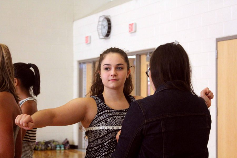 As the dancers are waiting for practice to start, they are also taking turns getting measured for their team uniforms. Junior Megan Deming was one of the first ones to get measured and then return back to the rest of the team to begin stretching.