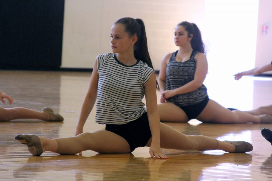 Stretching at the first Dance team practice of the year, sophomore Alaina Combs does the splits and prepares for their first dance.