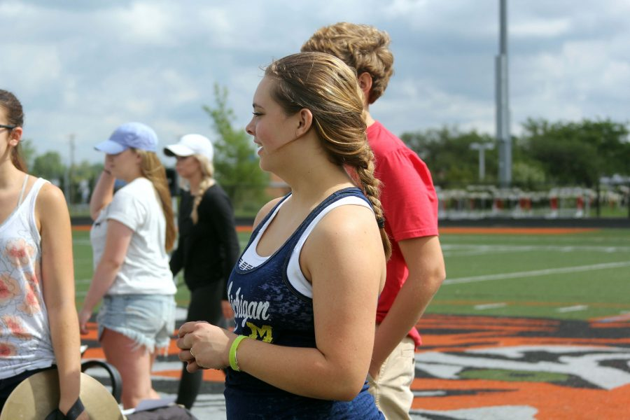 Waiting for band practice to start, senior Karmyn Long laughs along with the other members of the drum line.