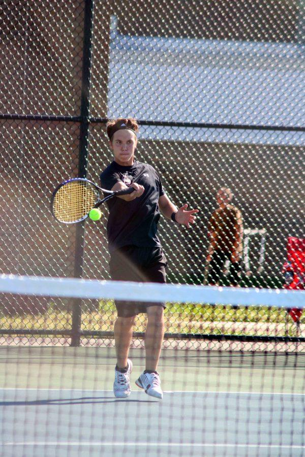 Junior Connor Griffin hits the ball during their   match. Connor successfully helped Fenton gain a victory against the opposing team, Lapeer.