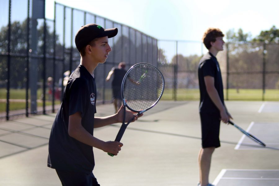 Freshman Trevor Bloss focuses on the tennis ball while playing doubles with fellow teammate, junior Will Galvin.