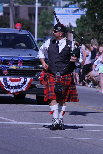 Teacher, Mr.Wright, plays his bagpipes during the July 4th parade.