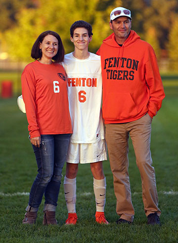 During half-time of our Fenton varsity soccer's very last home game, junior, Owen O'brien stands between his mother and father after he spoke into a microphone, thanking them for loving him and supporting him throughout his first varsity soccer season.