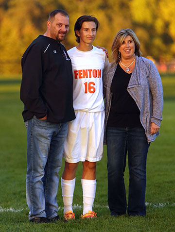 During half-time of the Fenton varsity soccer game against Flushing, junior, Tristan Przybylowicz stands between his parents Jamie Przybylowicz (right), and Eric Przybylowicz (left) and smiles after thanking his parents for everything that they have done for him throughout his very firsy varsity soccer season.