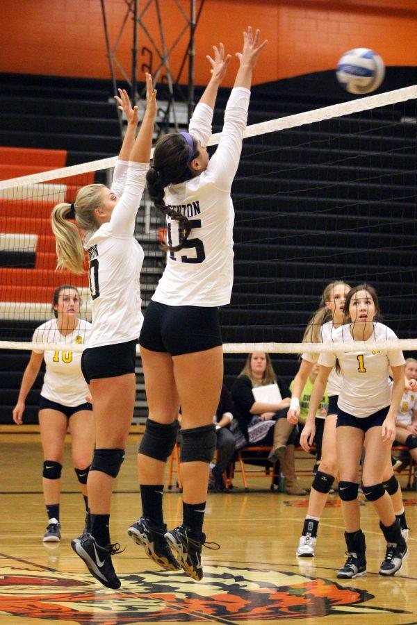 Trying to stop the opponents serve, sophomore Delaney Meisch and teammate,  senior Lily Elfstrom jump higher than the net. Meisch then succeeded and smacked the opponents ball back onto their side, scoring a point for the lady tigers.