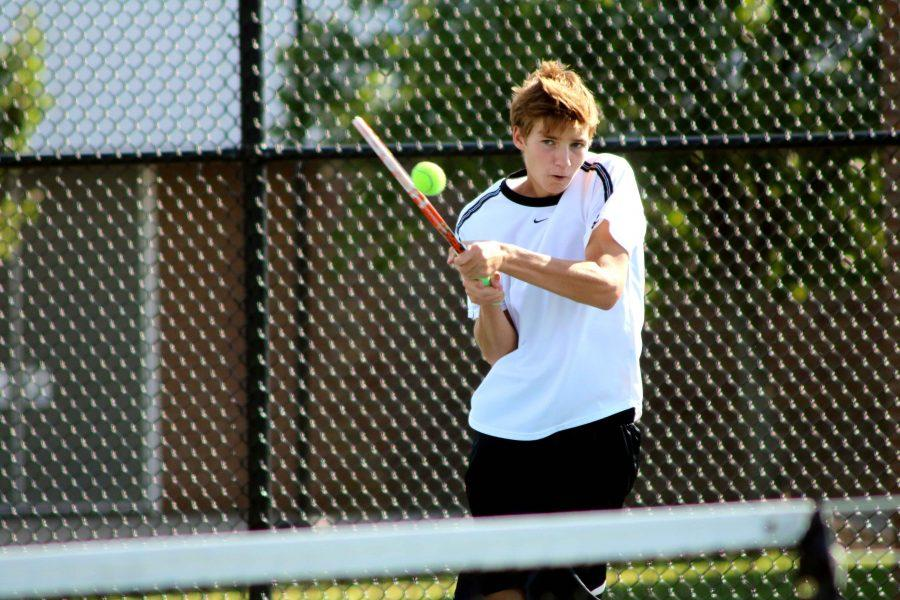 Leaping into the air to hit a tennis ball, junior Baylor Hamilton practices with his Varsity Tennis teammates.