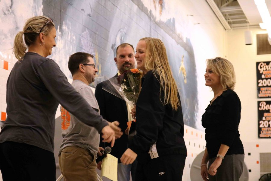Proud of her accomplishments, senior Lauren Gruber gets congratulated by her coach. After all the senior swimmers received the gifts presented by their coaches, the girls approach the home starting blocks for one last jump.