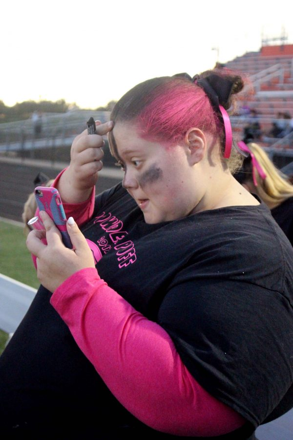 Before the annual homecoming week event powder puff, senior Abigail Hager, prepares for the game. Abigail adds eye black down her nose and under her eyes for more affect.