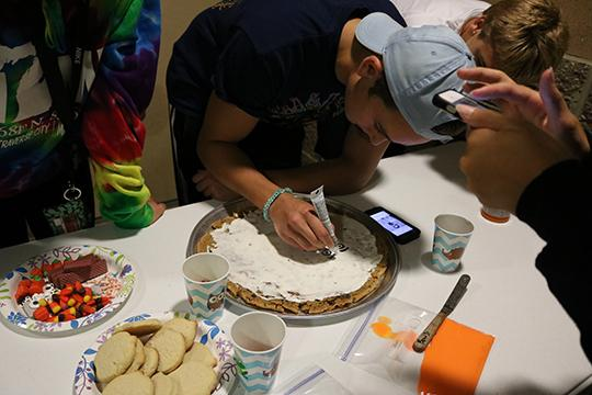 Senior Brennen Henson leads his team, team La Bren Bren to victory in the annual cookie decorating contest at the ball run camp out. He and his fellow senior teammate Brenna Bleicher take on the task of drawing their three coaches in icing.