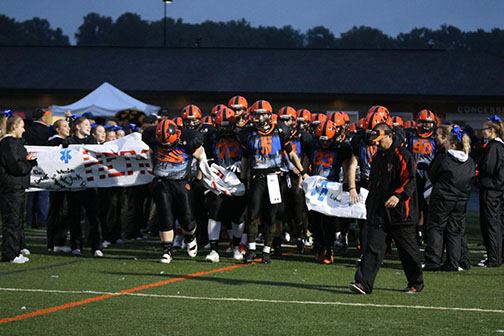 Breaking through the banner, junior Josh Czarnota along with the rest of the varsity football team prepare for the Hometown Hero's game against Holly. Playing through the rain Fenton defeated Holly with a score of 54-35.