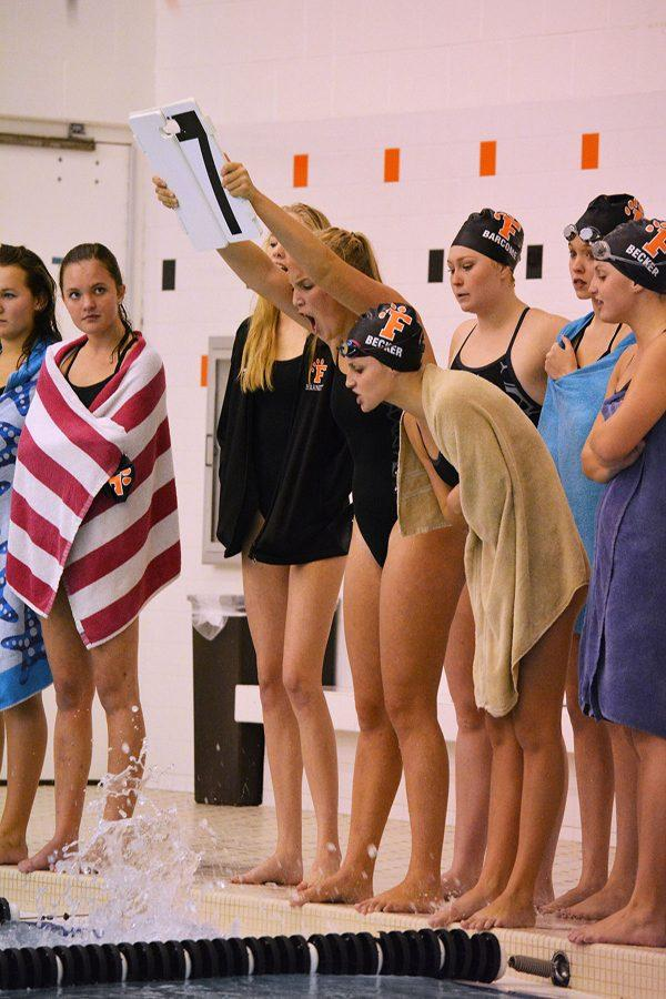 As Senior Lauren Gruber counts for Senior Elise Cassidy while she swims the 500 backstroke during the 500 freestyle at their meet last week. Fenton won that meet against Holly while Cassidy placed second in her event.