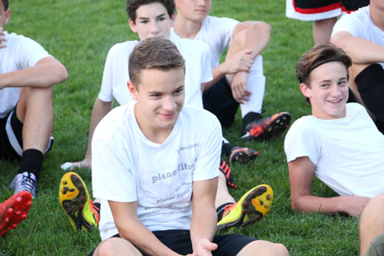 Sitting next to his teammates during practice, senior Nolan Suydam listens to his coach. The soccer players split into two teams and competed against each other. The losing team had to buy Buffalo Wild Wings for the winning team.