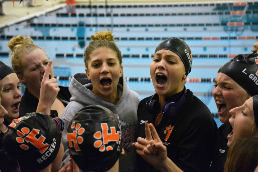 Cheering along with her fellow teammates senior Elise Cassidy leads the girls swim team in their last cheer of the season. The girls dominated metros saturday afternoon with a total of 772 points winning the metro title for the thirteenth straight year.