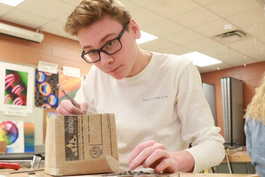Junior Lars Angel sculpts a figure into his slab of clay for his most recent project.
