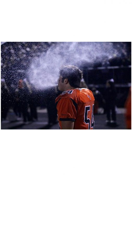 Junior Tyler Macintosh hydrates after coming off of the field.