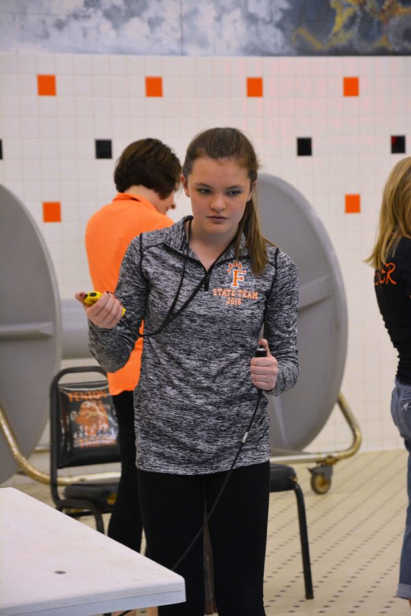 During the boys swim meet on Tuesday, sophomore Sabrina Hall times for the swimming events. Hall is a swimmer for the girls swim team during the fall sports season, and this year she traveled to states with some of her fellow teammates.