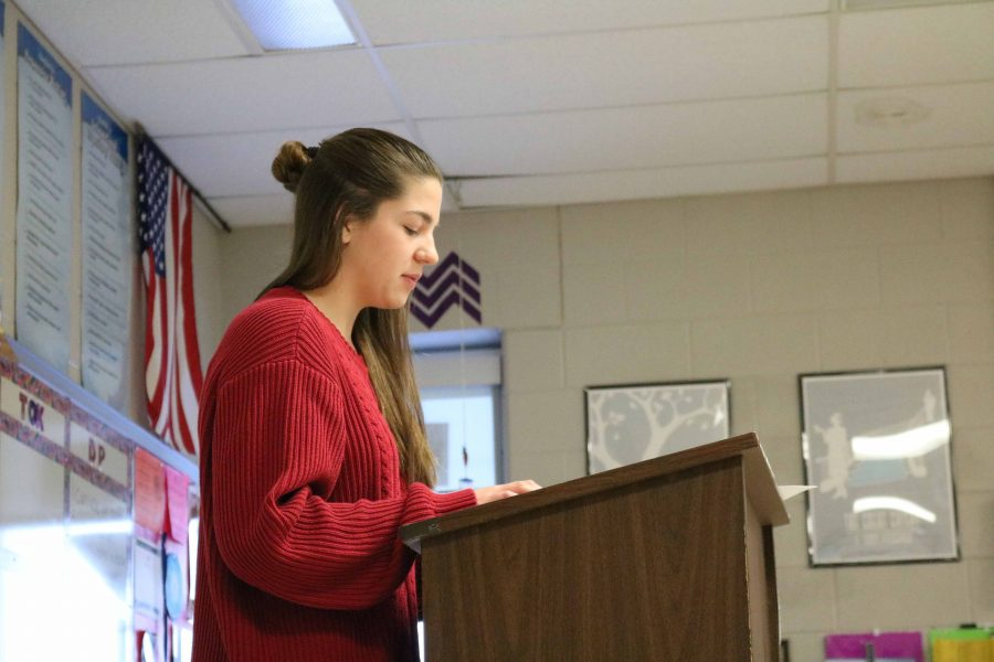 Leaning against the podium, sophomore Lauren  Koscielniak prepares to read her poem for Honors American Studies. Koscielniak and her classmates were tasked with writing poems about historical figures from the Fenton area and presenting them along with some background on the person they chose.