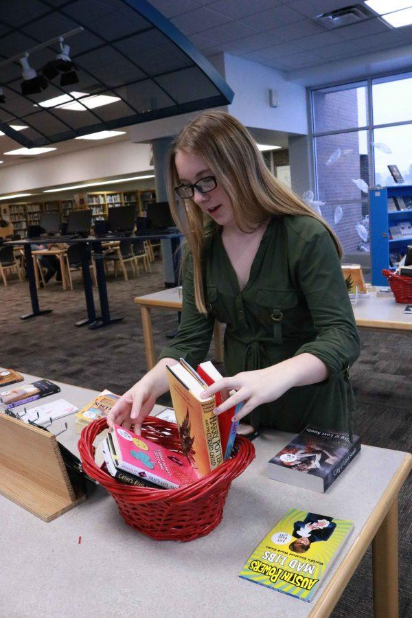 During her media service class, sophomore Jenna Thornton straightens up the book fair that was taking place in the library.