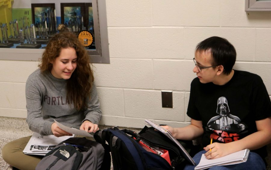 Juniors Cassie Menzies and Joe Amberg work on homework before classes begin for the day. The friends regularly find a spot in the halls to discuss assignments.