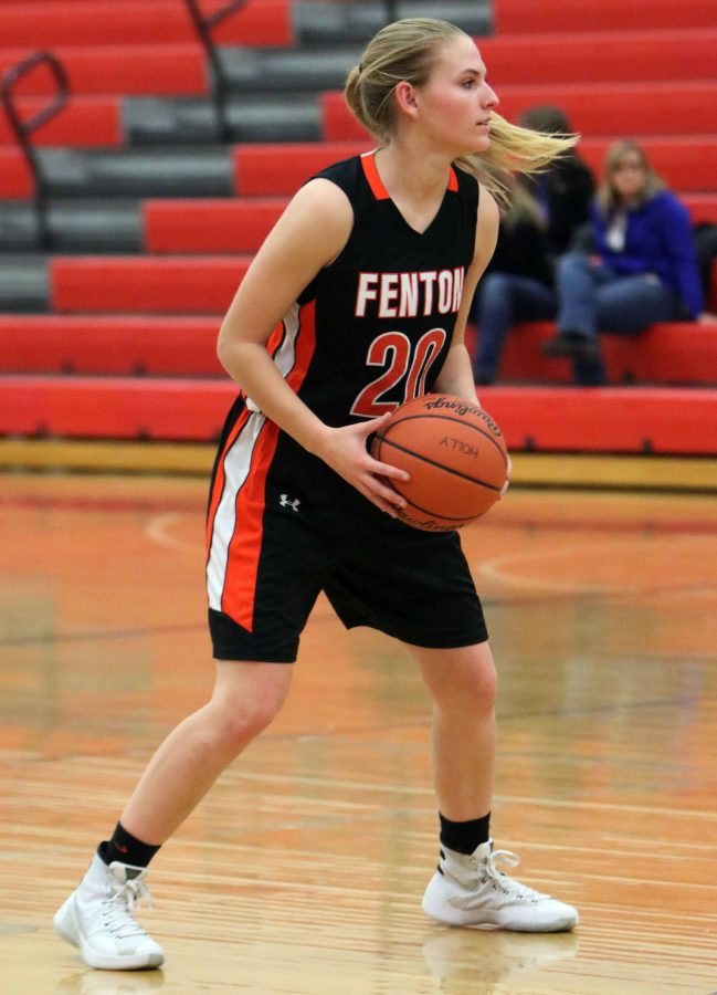 Sophomore Erin Carter looks across the court for an open teammate to pass the ball to in her JV basketball game against Holly.