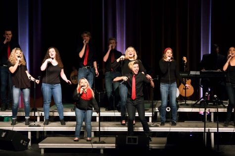 With microphones held high and eyes aimed towards the crowd the Ambassadors perform at their annual 'Sneak Preview. ' back By Popular demand' will be Feb. 24 and 25 at 7:30 p.m., tickets will be sold at the door for $8.