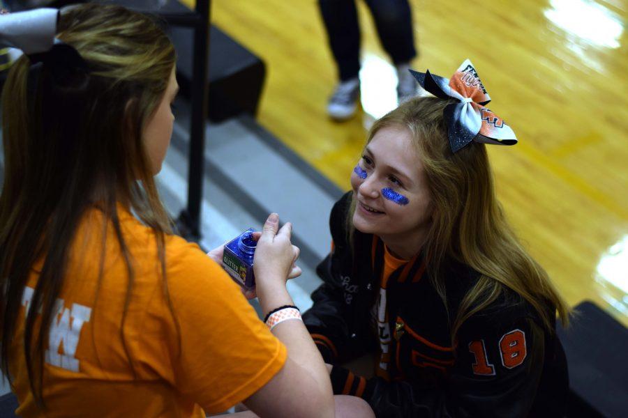 Freshman Maeve Smith prepares junior Rachael Roman to cheer on their Flint Metro League sister team Flint Kearsley.