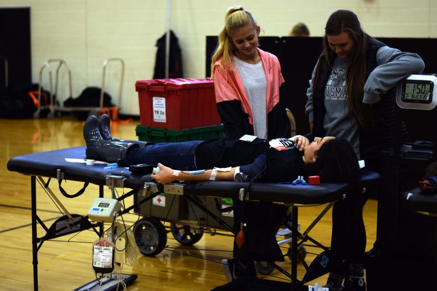 As junior Ariana Mansour gives blood, her friends seniors Kylie Aldred and Ellie Reuschlein keep her company through the process.
