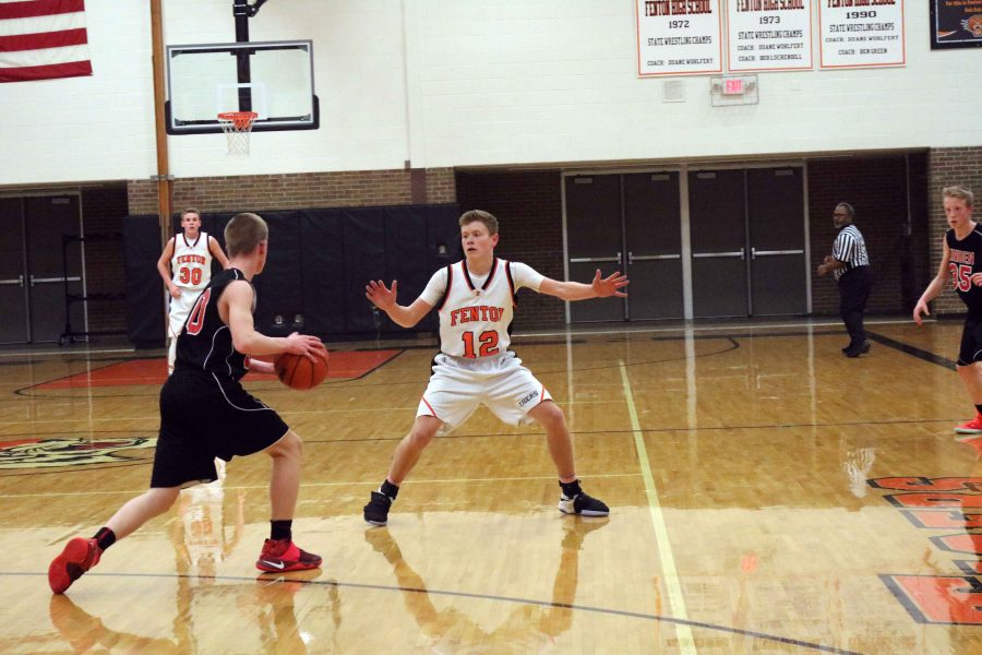 Guarding the ball, freshman Alec Kussro assists his team during their game against their rivals, Linden, on Feb. 23.