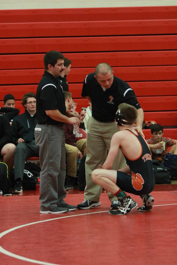 During his wrestling meets, Jake Church gets tips on how to pin his opponent from his coaches.