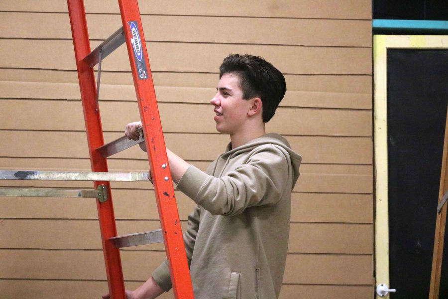 Climbing a ladder, senior Chase Raymond prepares to help other members of IB Theatre build a house as part of their set in the black box. They've spent last week building the set for their production of To Kill a Mockingbird which has its opening show on Thursday, Feb. 2 at 7:30.