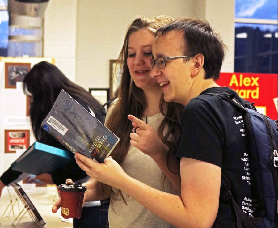 Juniors Joe Amberg and  Olivia Blumenschein observe the American Library Association award winning books displayed in the media center  this morning. In addition to the books, a coffee bar was offered to participants.