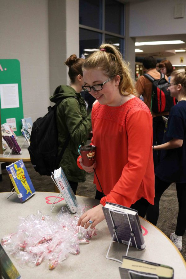 Looking at the presentation boards displaying book award winners, sophomore Jenna Thornton looks at the treat giveaways. Due to February being love your library month, our high school media center put on a coffee bar for students and staff in the morning before school.